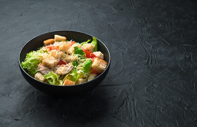 Traditional caesar salad with crackers, lettuce leaves and chicken breast on a black background. side view with copy space. healthy food.