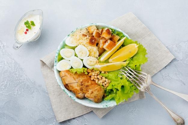 ウズラの卵と松の実を軽いセラミックボウルに入れた伝統的なシーザーサラダ。灰色の石またはコンクリートの表面に。ランチボウル。セレクティブフォーカス。上面図。