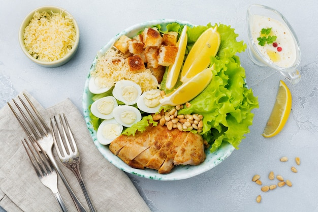 ウズラの卵と松の実を軽いセラミックボウルに入れた伝統的なシーザーサラダ。灰色の石またはコンクリートの表面に。ランチボウル。セレクティブフォーカス。