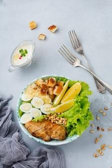 Традиционный салат «цезарь» с перепелиными яйцами и кедровыми орехами в светлой керамической миске на серой каменной или бетонной поверхности.