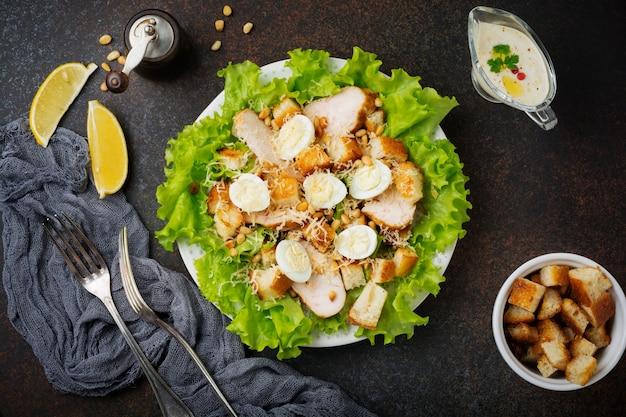 Традиционный салат «цезарь» с перепелиными яйцами и кедровыми орехами в светлой керамической миске на темной бетонной поверхности