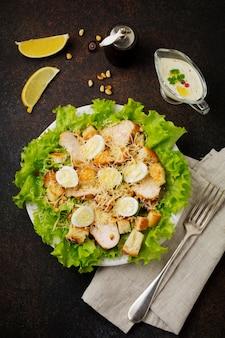 ウズラの卵と松の実を暗い石またはコンクリートの表面にある明るいセラミックボウルに入れた伝統的なシーザーサラダ。セレクティブフォーカス。
