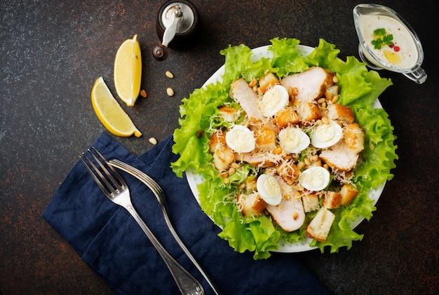 Традиционный салат «цезарь» с перепелиными яйцами и кедровыми орехами в светлой керамической миске на темной каменной или бетонной поверхности.