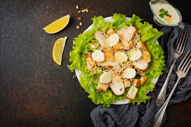 Traditional caesar salad with quail eggs and pine nuts in a light ceramic bowl on dark stone or concrete background.