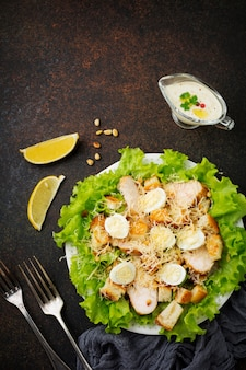 Traditional caesar salad with quail eggs and pine nuts in a light ceramic bowl on dark stone or concrete surface