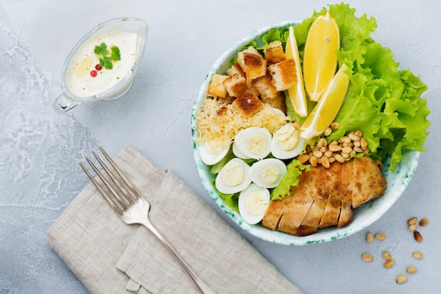 Traditional caesar salad with quail eggs and pine nuts in a light ceramic bowl on a gray concrete surface