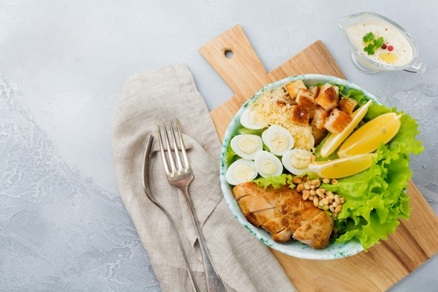 Traditional caesar salad with quail eggs and pine nuts in a light ceramic bowl on a gray stone or concrete background.