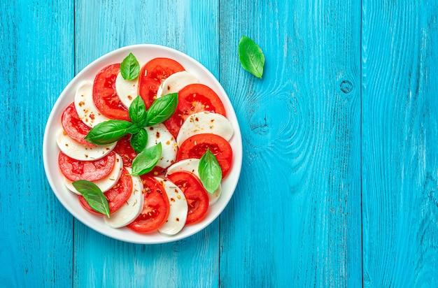 Традиционный салат капрезе с памидором, мацареллой, базиликом и оливковым маслом на голубом фоне. итальянская кухня. вид сверху, пространство для копирования.