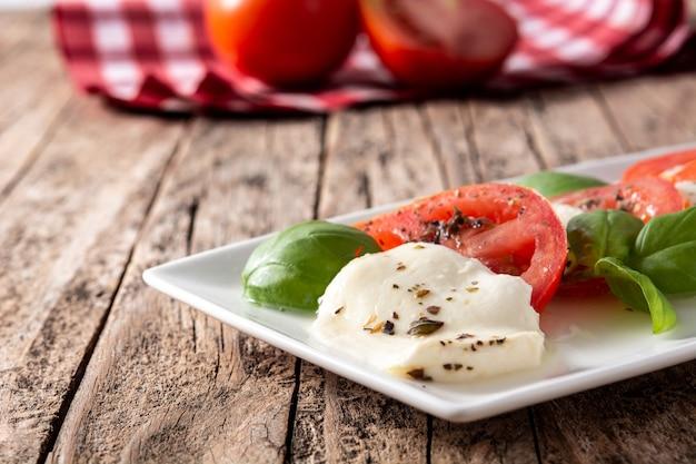 素朴な木製のテーブルにトマトとモッツァレラチーズの伝統的なカプレーゼサラダ