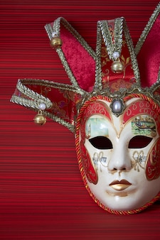 Traditional carnival venetian mask with rich decor on a red background, selective focus