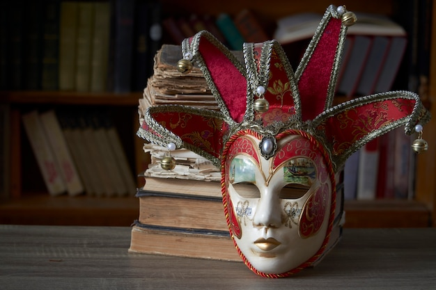 Traditional carnival venetian mask with rich decor on a wooden table in the library, selective focus