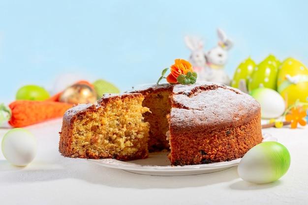 粉砂糖にんじんの花とミントで飾られた伝統的なキャロットケーキイースター休暇のためのデザートのコンセプト