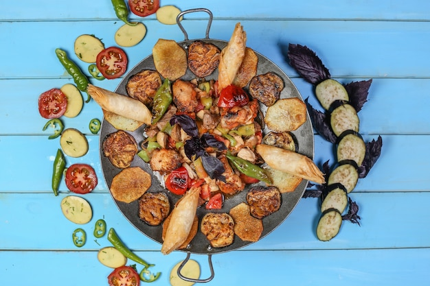 Traditional caucasian sac ichi with grilled meat and vegetables