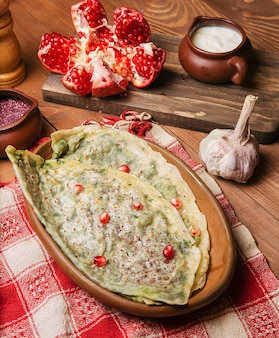 Traditional caucasian vegetable gutab, kutab, gozleme with sumakh, granate seeds and yogurt in wooden plate