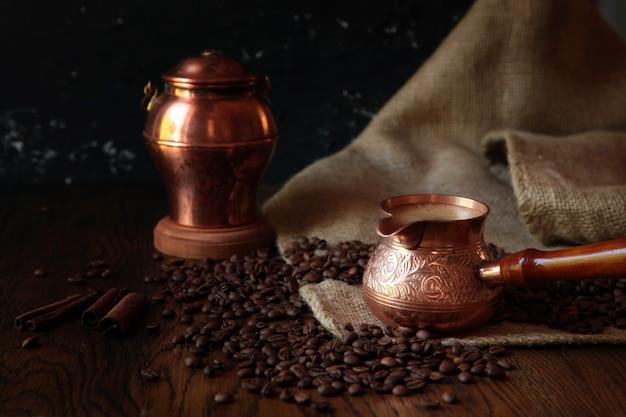 오래된 녹슨 배경에 전통적인 cezve 컵의 커피, 가방, 국자. 어두운 음식 사진.
