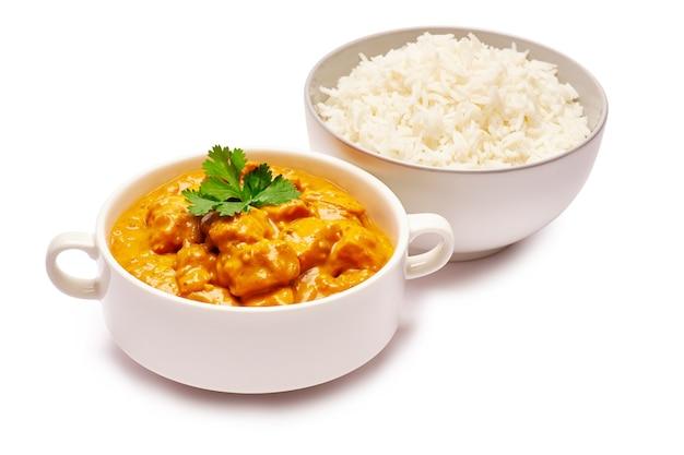 Традиционное куриное карри и миска отварного риса изолированы
