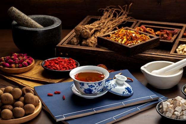 テーブルの上の伝統的な中国の健康茶と古典的な医学書