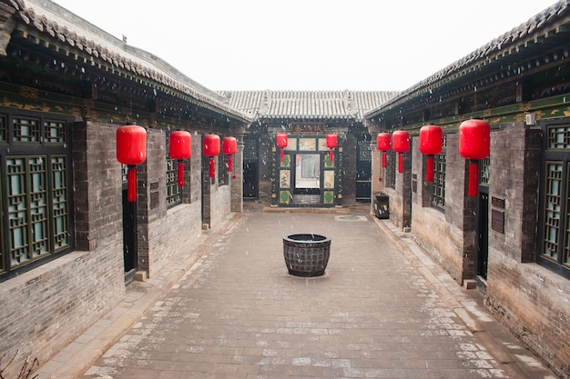 Traditional chinese house with red lanterns and snow