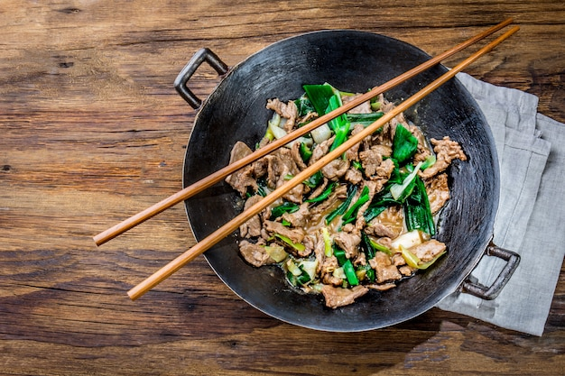 Traditional chinese mongolian beef stir fry in chinese cast iron wok with cooking chopsticks