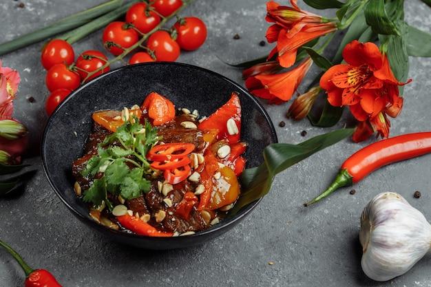 伝統的な中国のモンゴルビーフ炒め物と中国の鋳鉄鍋で箸を調理