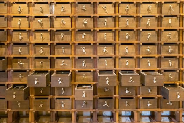 繁体字中国語の薬局。背景の古代ハーブ薬局キャビネット木製引き出し