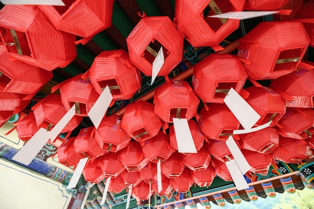Traditional chinese red lantern with white paper hanging on ceiling of temple