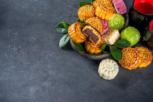伝統的な中国の甘いデザート。自家製の中国の雪の皮と焼き月餅、中国の中秋節の食べ物、カラフルな餅、フラットレイの上面図のコピースペース