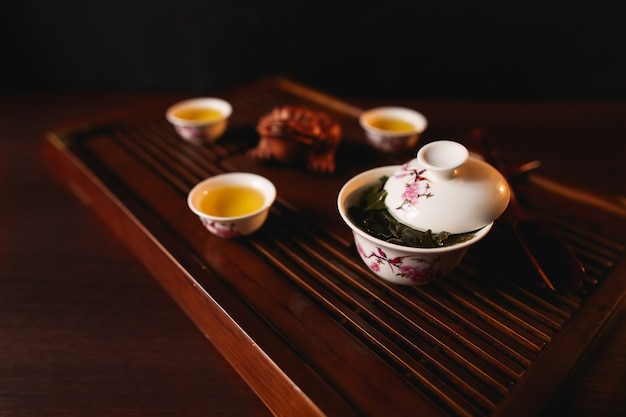 The traditional chinese tea ceremony. porcelain gaiwan and three cups on a tea desk chaban