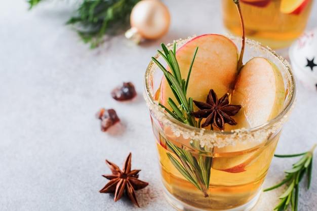Традиционный рождественский яблочный пунш с корицей, анисом и веточками розмарина на светлом фоне. селективный f â¾cus. вид сверху.