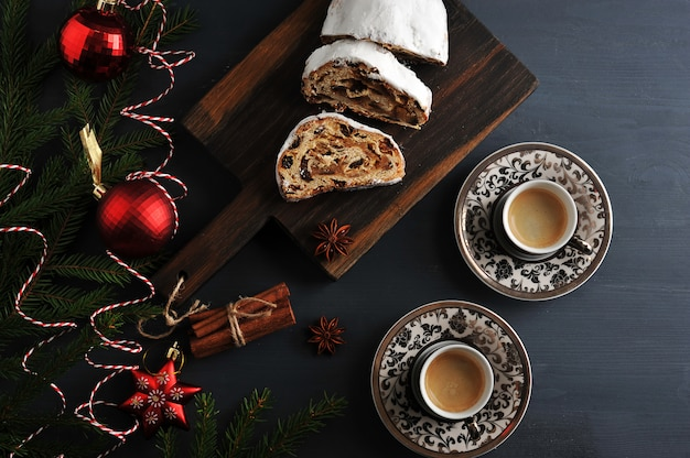 Traditional christmas cake pie with raisins and nuts with tree branches and toys, and two cups of coffee