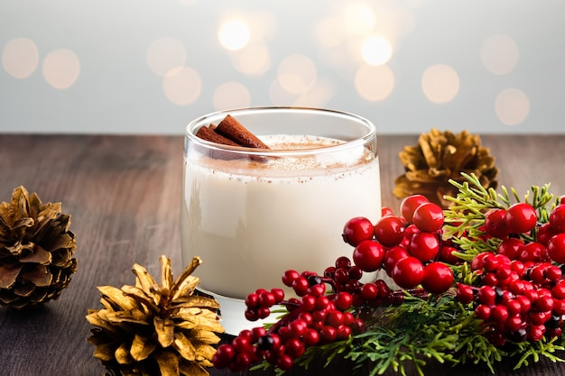 계란, 알코올, 강판 육두구 및 계피 근접 촬영과 함께 전통적인 크리스마스 칵테일 eggnog. 붉은 장식과 황금 솔방울이 있는 테이블에 크리스마스와 겨울을 위한 달콤한 전통 음료
