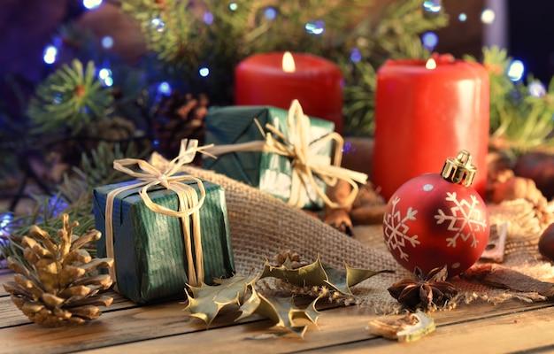 Традиционное рождественское украшение на деревянном столе со свечами, подарочной коробкой и огнями