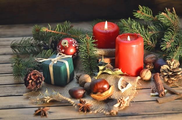 Традиционное рождественское украшение на деревянном столе со свечами и подарочной коробкой