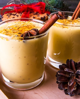 Traditional christmas drink eggnog on a wooden background