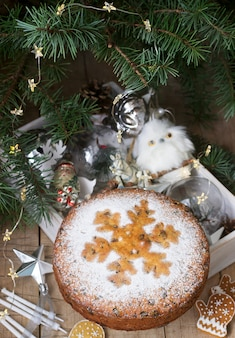 Traditional christmas fruitcake on  a box with christmas toys and fir branches.