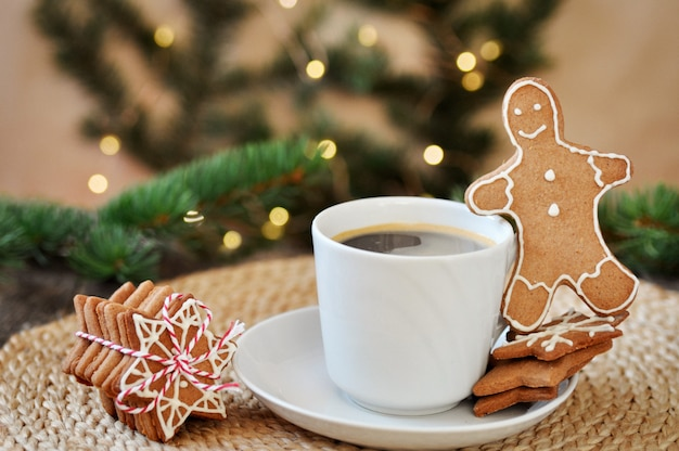 Traditional christmas gingerbread sugar frosting shaped like a funny little man and a cup of hot espresso on wooden.