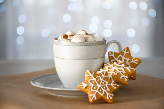 Traditional christmas homemade gingerbread cookie and cup of hot winter drink with marshmallow and bokeh lights on background.