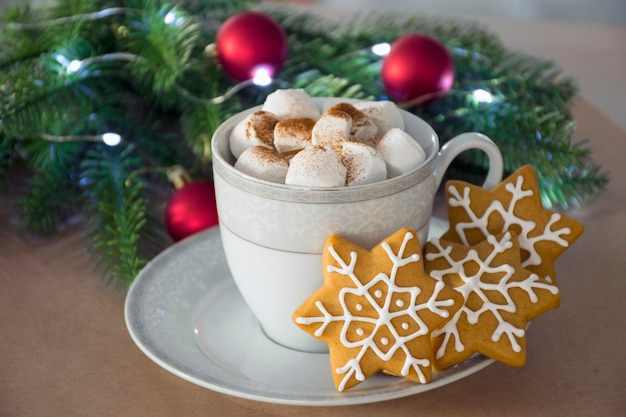 Traditional christmas homemade gingerbread cookie and cup of hot winter drink with marshmallow and festive decor on background.