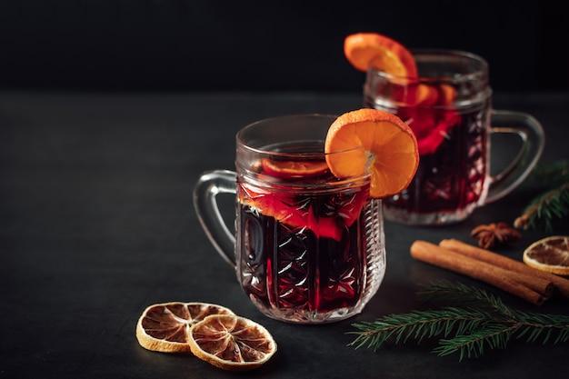 伝統的なクリスマスのホットホットワイン。暗い背景にガラスのカップにスパイスと温かい飲み物。