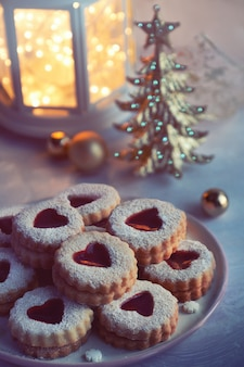 Traditional christmas linzer cookies filled with red jam on light table with xmas decorations