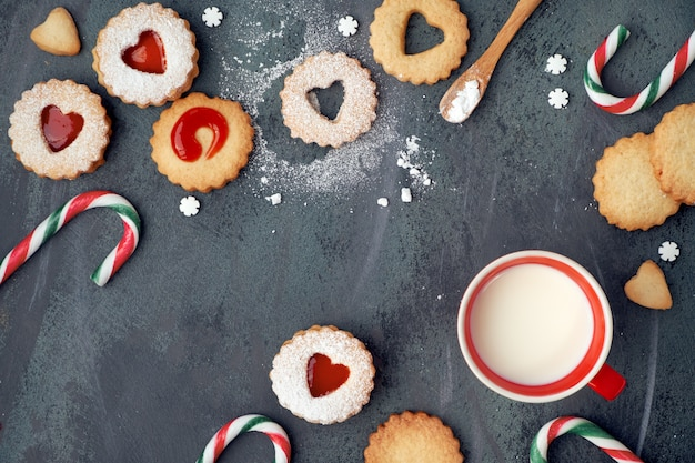 Traditional christmas linzer cookies with strawberry jam, candy canes and milk on dark