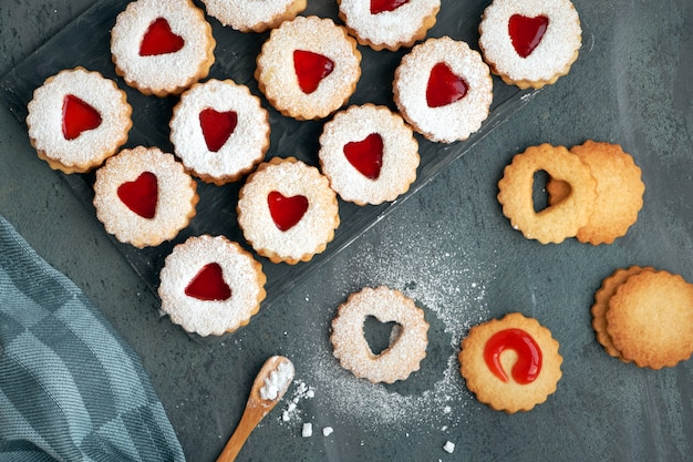 Traditional christmas linzer cookies with strawberry jam in wooden tray on dark background