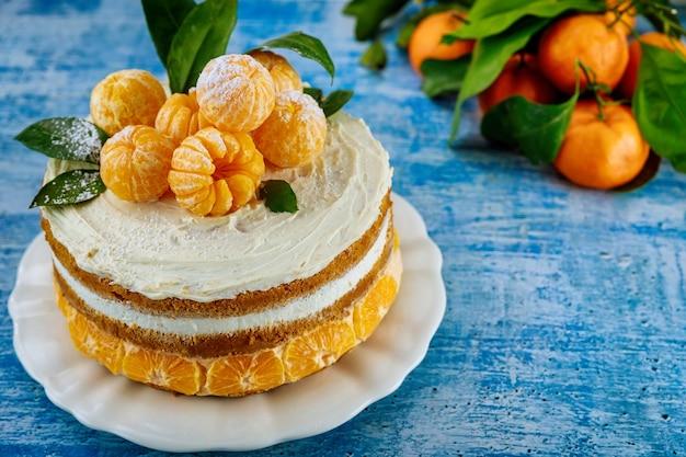 Traditional christmas naked cake with fresh mandarins on blue background.