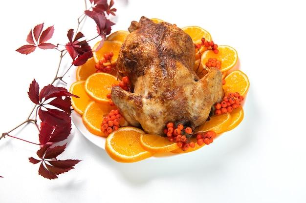 伝統的なクリスマスまたは感謝祭のローストターキー、オレンジ色のフルーツスライスと白い背景で隔離のナナカマドの果実を添えて