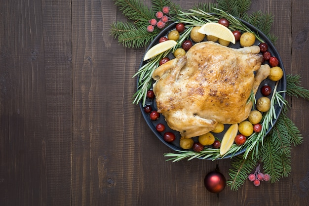 Traditional christmas roasted chicken with potatoes and rosemary on wooden table. top view.