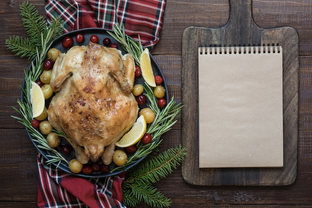 Traditional christmas roasted turkey with spices and rosemary on wooden table.