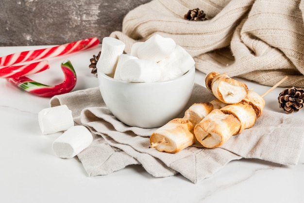 Traditional christmas sweets  candy cane, marshmallow and baked on fire marshmallow skewers on white , copyspace