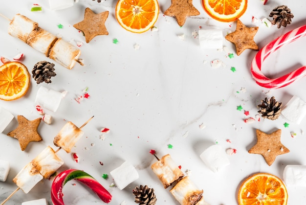 Traditional christmas sweets  candy cane, marshmallow, dried orange, gingerbread stars, baked on fire marshmallow skewers on white marble , copyspace top view