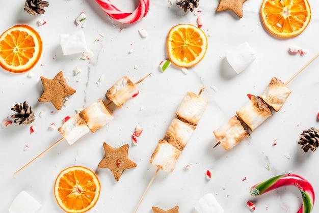 Традиционные рождественские сладости конфета, зефир, сушеный апельсин, пряничные звезды, запеченные на огне шашлык из зефира на белом мраморе, вид сверху