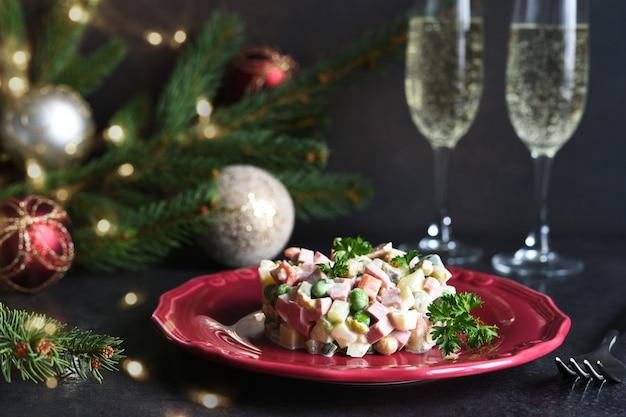 Традиционная рождественская сервировка стола с салатом оливье, бокалами шампанского и украшениями